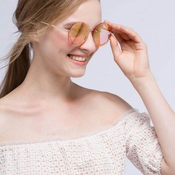 Girl wearing pink tinted sunglasses with a subtle metal smiley face frame.